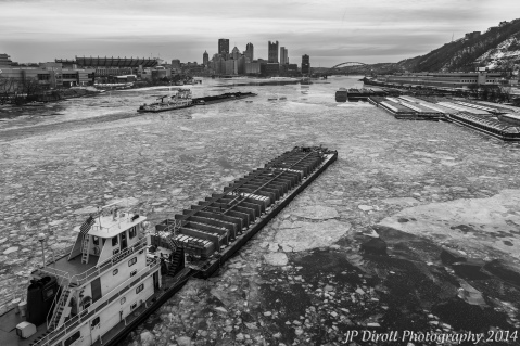 A coupe of barges break up the ice along the Ohio River.