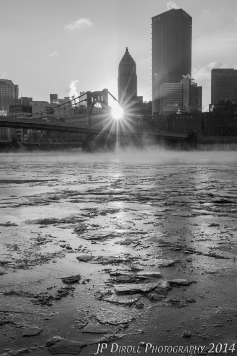 The sun shines through the Andy Warhol Bridge over the frozen river in Pittsburgh.