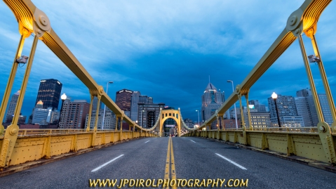 """EXHIBIT 1:  This first view is just above eye level.  My camera is about 1 foot over my head (and I'm 6'2"""") and pointed slightly up.  With this perspective you get a broad view of the skyline with the bottoms of the buildings not being obstructed by the sides of the bridge.  The center line is present, but not prominent, in the image and serves as a leading across the bridge and into the city."""