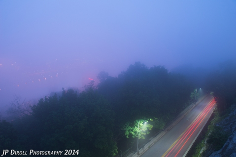 Dense twilight fog blankets the city, blocking any view of the skyline.